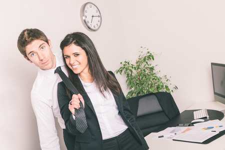 Bully Businesswoman Holding Colleagues Necktie photo