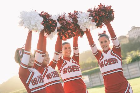 cheerleader: Group of Cheerleaders with Raised Pompom Stock Photo