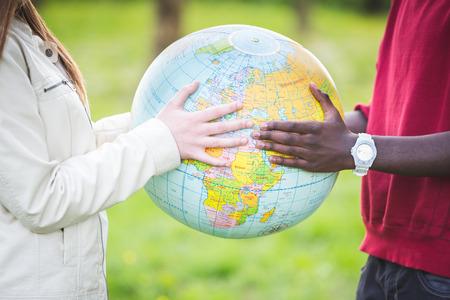 Multiracial Teen Couple Holding Globe Map Stock Photo