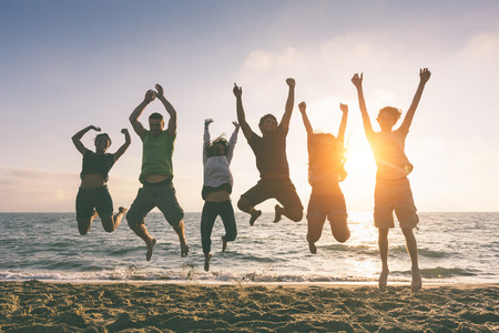 multiracial group: Grupo multirracial de que saltan en la playa, luz de fondo