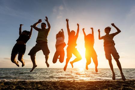 personas saltando: Grupo multirracial de que saltan en la playa, luz de fondo