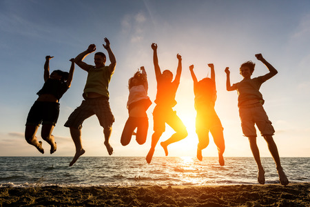 Multiracial Group of People Jumping at Beach, Backlight Imagens