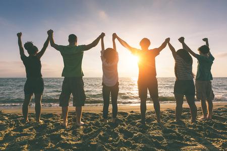 manos levantadas: Grupo multirracial de las personas con los brazos levantados mirando la puesta del sol