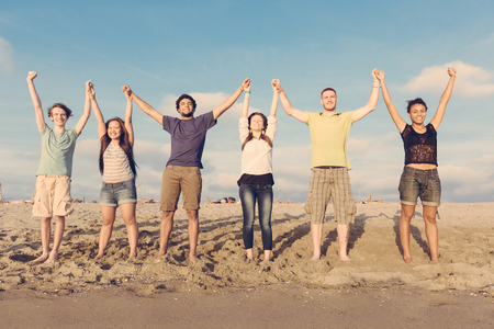 raised arms: Multiracial Group of People with Raised Arms looking at Sunset Stock Photo
