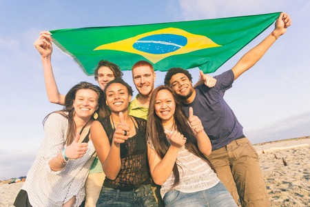 integrated groups: Group of Friends with Brazilian Flag at Beach Stock Photo