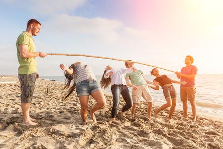 Freunde tanzen Limbo am Strand