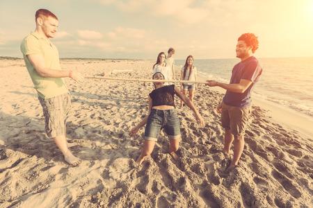 Friends Dancing Limbo at Beach photo