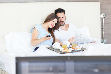 hotel suite: Couple Watching TV at Hotel Room Stock Photo