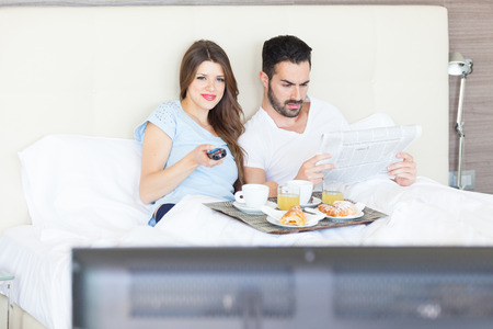 Couple Watching TV at Hotel Room photo