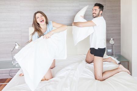 pelea: Feliz pareja con Pillow Fight en el Hotel Room Foto de archivo