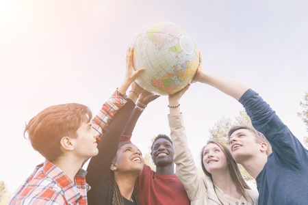 世界世界のマップを保持しているティーンエイ ジャーのグループ