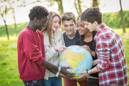 世界の世界地図を保持している 10 代の若者のグループ 写真素材