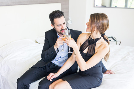 man in suite: Elegant Young Couple Cheering at Hotel Suite