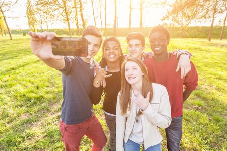 femme qui rit: Amis adolescents qui prenaient Selfie au parc