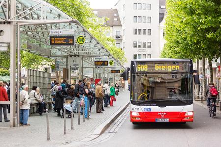 parada de autobus: BONN, Alemania - el 06 de mayo 2014: Personas esperando el autobús en la parada de autobús en Friedensplatz