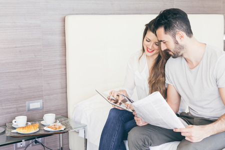 hotel suite: Couple with Digital Tablet and Newspaper