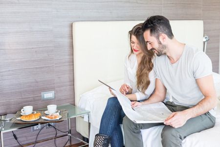 breakfast room: Couple with Digital Tablet and Newspaper