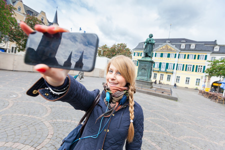 German Girl Taking Selfie in Bonn Main Square photo