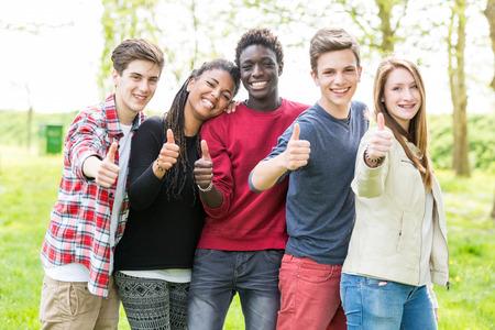 Grupo multiétnico de adolescentes con los pulgares para arriba