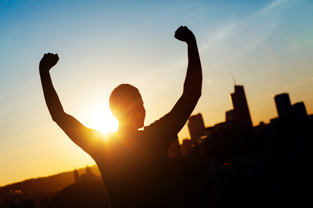 arm outstretched: Successful Man with Raised Arms at Sunset Stock Photo