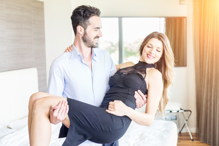 man carrying woman: Elegant Young Couple at Hotel Room Stock Photo