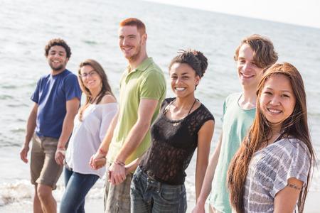 multiracial group: Grupo multirracial de Amigos Caminando en la playa