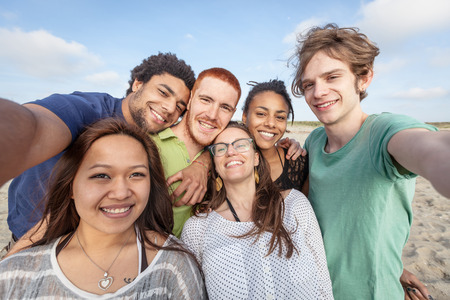 Multiracial Group of Friends Taking Selfie at Beach Stock Photo
