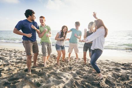 gente che balla: Gruppo multietnico di amici che hanno una parte in spiaggia