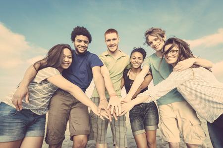 multiracial group: Grupo multirracial de amigos con las manos en pila Foto de archivo