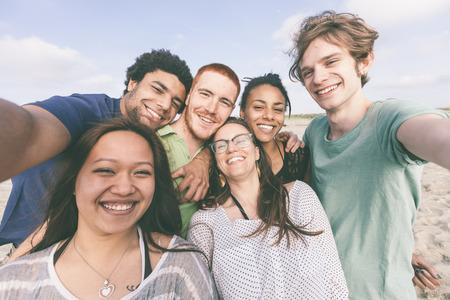 grupo de hombres: Grupo multirracial de amigos tomando Selfie en la playa