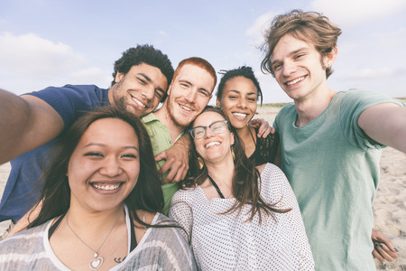 multiracial groups: Multiracial Group of Friends Taking Selfie at Beach Stock Photo