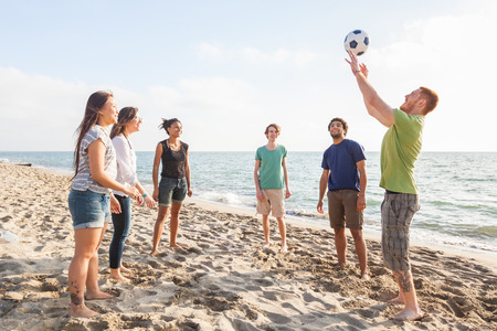 vacationers: Multiracial Group of Friends Playing Volleyball at Beach