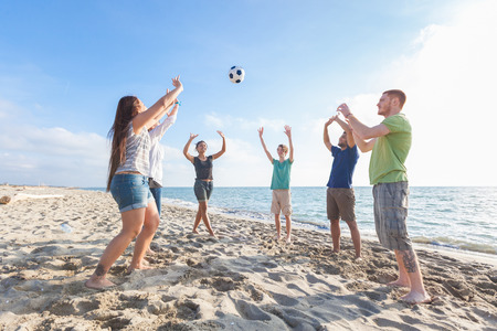 Multiracial Group of Friends Playing Volleyball at Beach photo