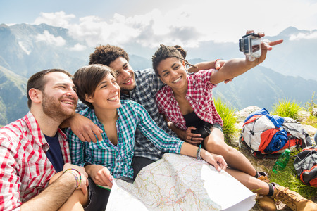 Friends Taking Selfie at Top of Mountain photo