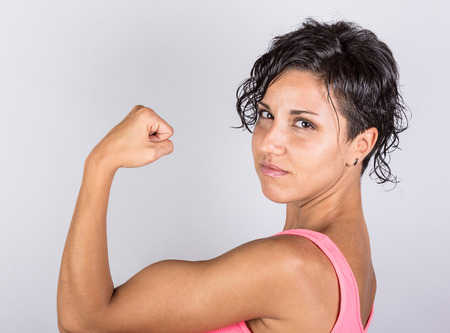 arm muscles: Funny Young Woman Showing Muscles
