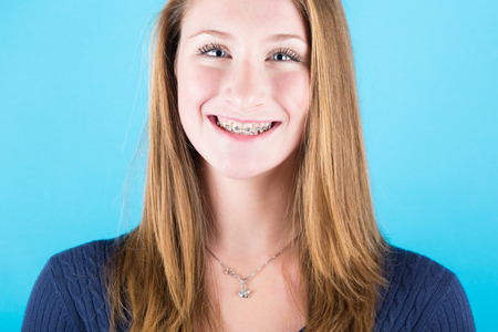 Smiling Beautiful Girl with Braces on Blue Background photo