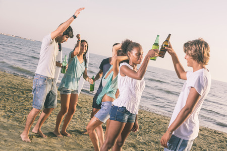 friends drinking: Group of Friends Having a Party on the Beach Stock Photo