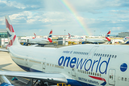 LONDON, UNITED KINGDOM - AUGUST 19, 2014  British Airways Boeing 747 at London Heathrow airport with rainbow and some more aircrafts on background