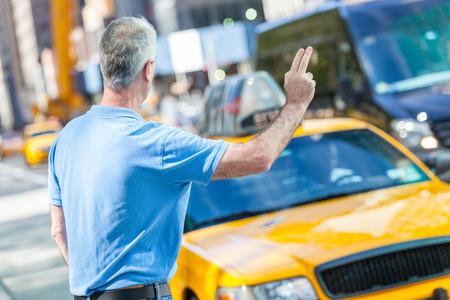 hailing: Senior Man Calling a Cab in New York Stock Photo