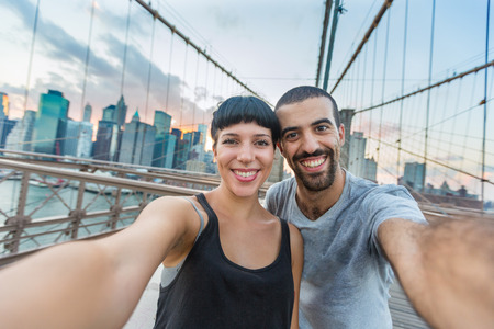 Young Couple Taking Selfie on Brooklyn Bridge photo
