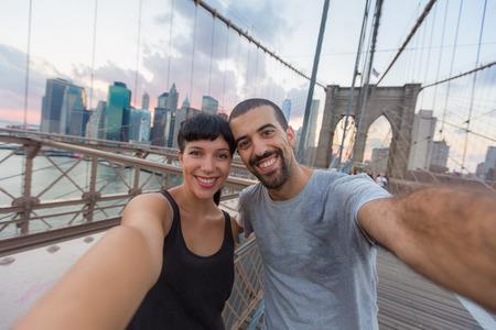 Young Couple Taking Selfie on Brooklyn Bridge photo