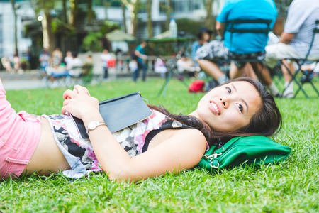 bryant park: Asian Girl Laying Down on the Grass at Park