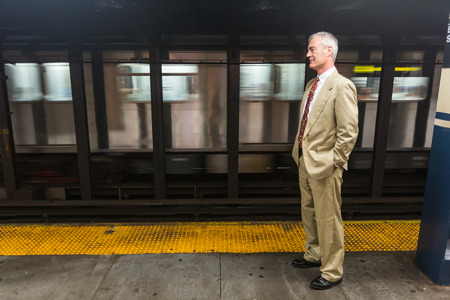 late sixties: Senior Businessman Waiting for the Train at Subway Station