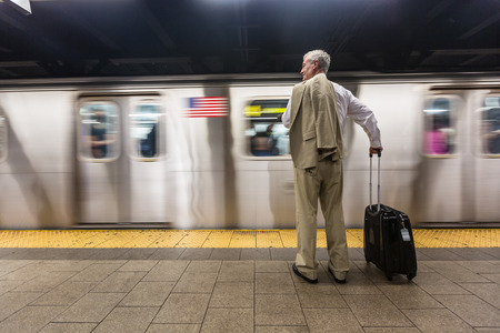 late 60s: Senior Businessman Waiting for the Train at Subway Station