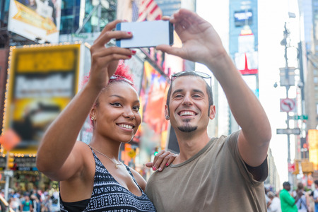 Young Couple Taking Selfie in Times Square Фото со стока