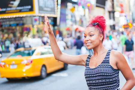 hailing: Beautiful Young Woman Calling a Cab in New York Stock Photo