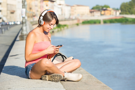 Beautiful Girl with Headphones and Mobile Phone in the City photo