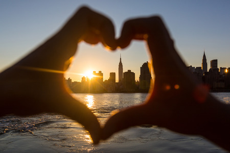 new york: Heart Shaped Hands at Sunset, New York Skyline on Background