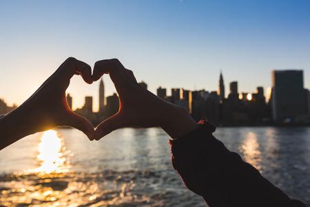 Heart Shaped Handen bij zonsondergang, New York Skyline op Achtergrond