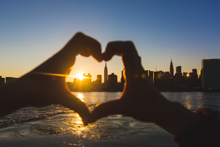new love: Heart Shaped Hands at Sunset, New York Skyline on Background